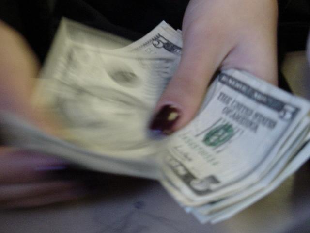 ruce přepočítávající bankovky